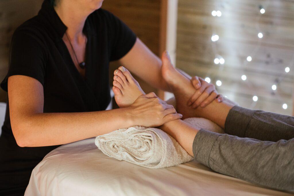 足のマッサージをしている女性セラピストの画像