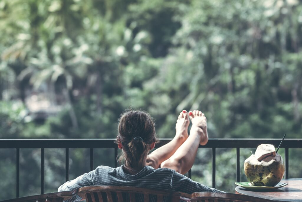 景色を座ってみている女性の後ろ姿の画像