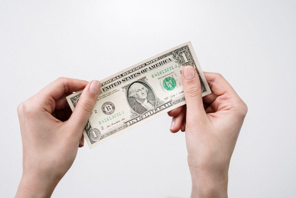 一ドル札を掲げている手元の画像