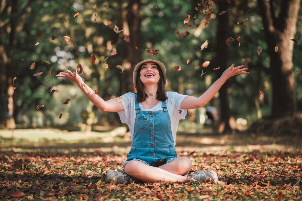 落ち葉で遊んでいる女性の画像