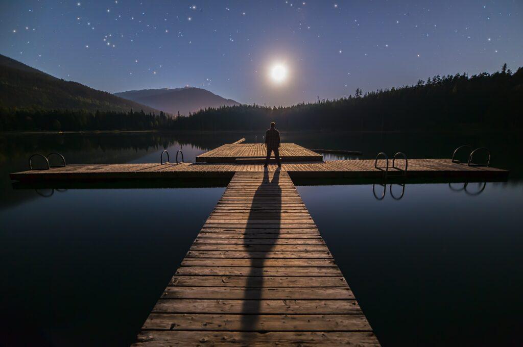 湖の真ん中に立つ人生経験豊富な男性の後ろ姿の画像