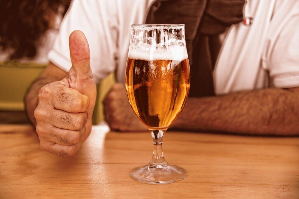 ビールの前でグッドポーズしている男性の画像