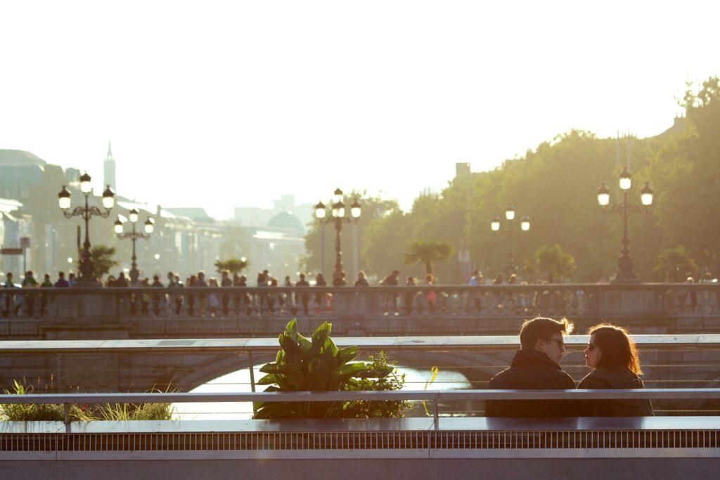 ベンチに座り見つめ合っているカップルの画像