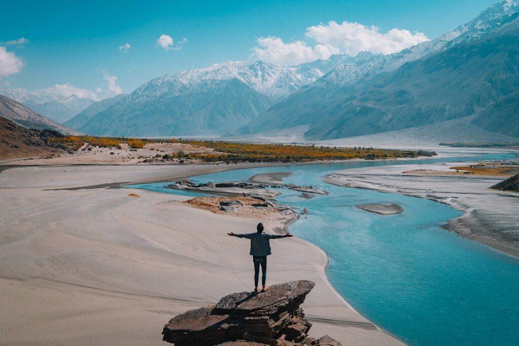川と山が見える大自然の中で両手を広げる男性の画像
