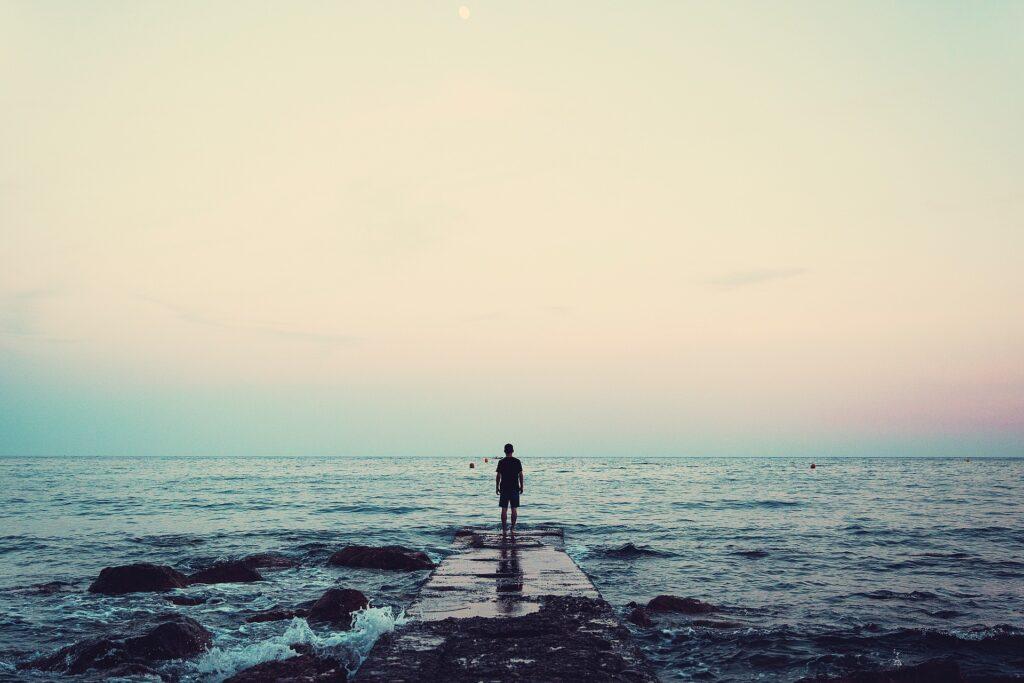 一人で海を見に来ている男性の後ろ姿の画像