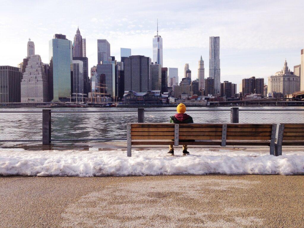 ニューヨークの街が見えるベンチに座っている男性の画像