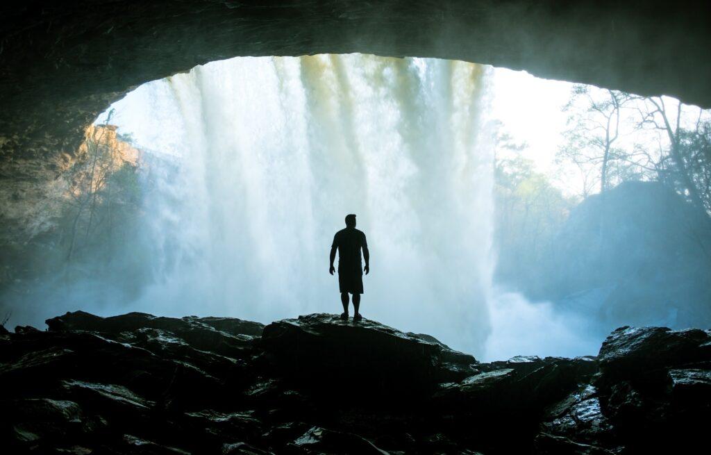 滝の見える洞窟を眺めている男性の後ろ姿の画像