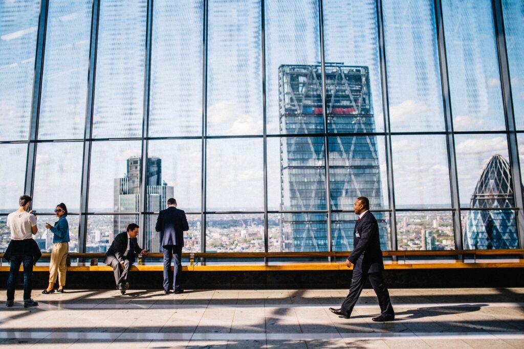 景色の良いビルの通路を歩いている男性の画像