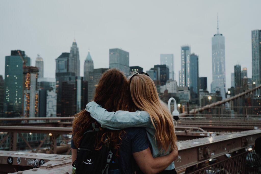 女子二人が仲良く身を寄せ合いながら街を眺めている画像