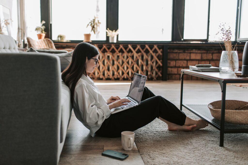 地べたに座りながら一人でパソコン仕事している女性の画像