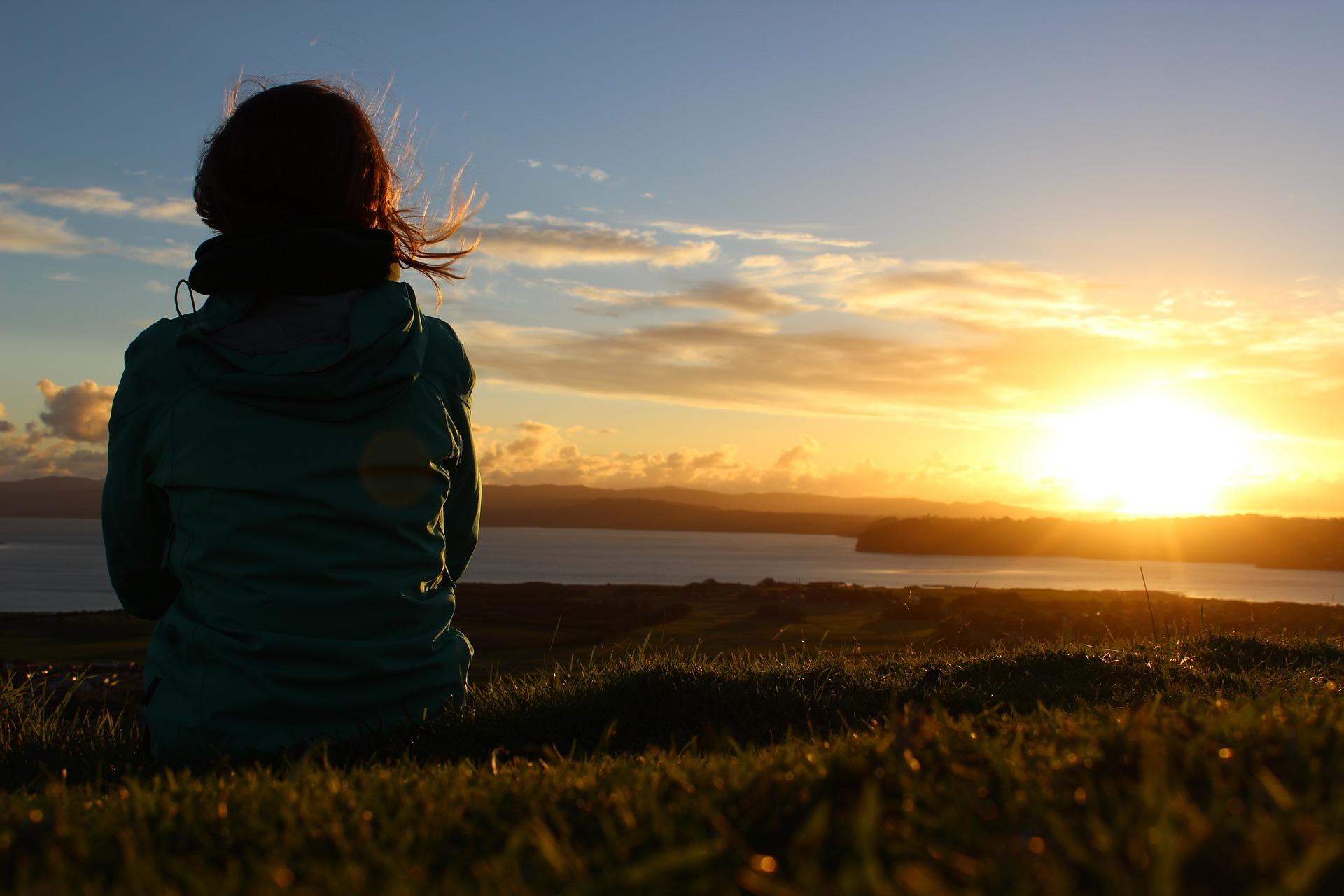 セラピストの仕事に悩んでいる女性が夕日を見つめている後ろ姿の画像