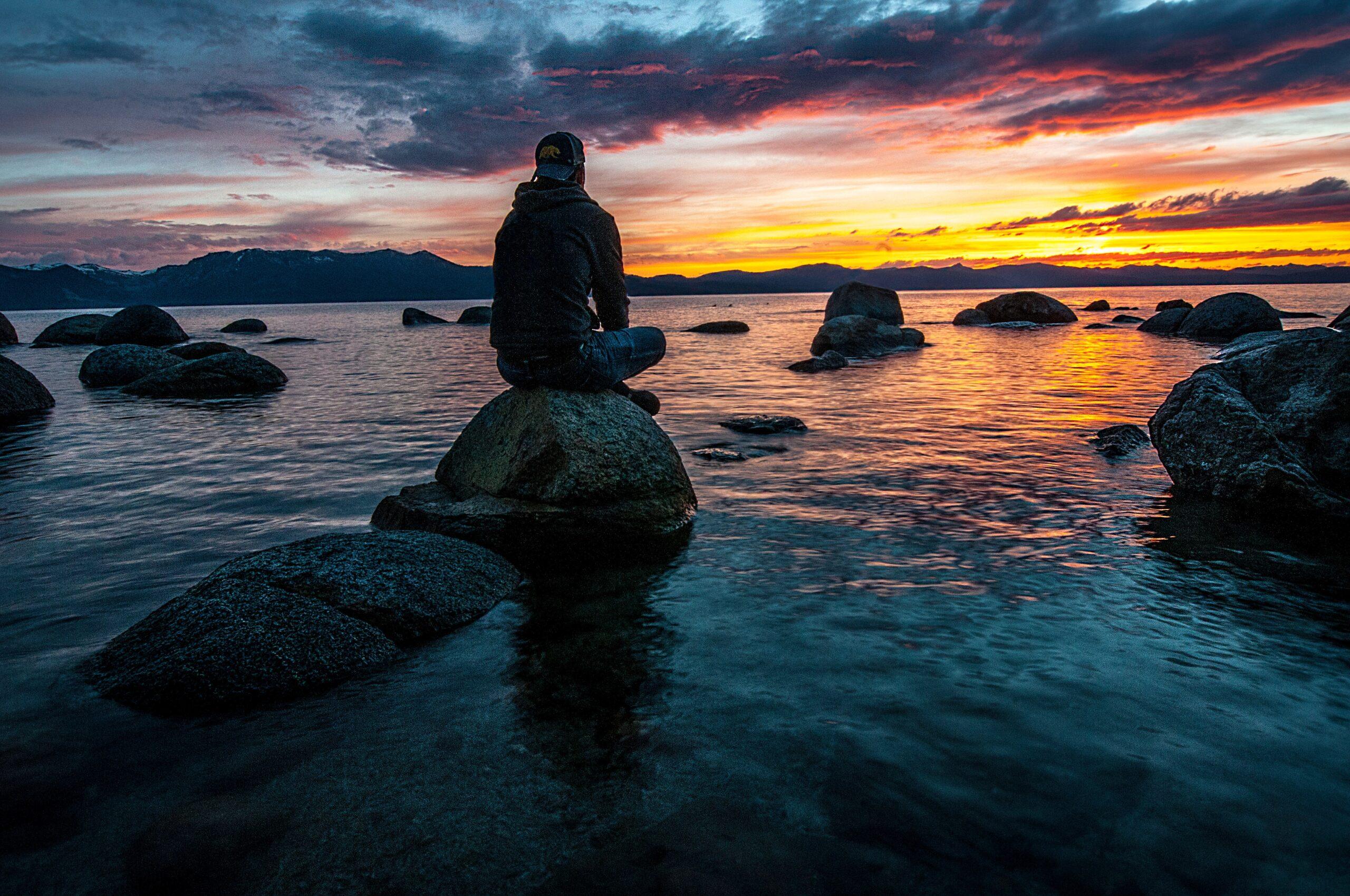 独身男が夕日を眺めて座っている画像